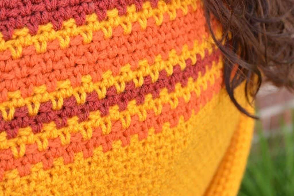 Close up of crochet linen stitch texture in burgundy, orange and gold stripes