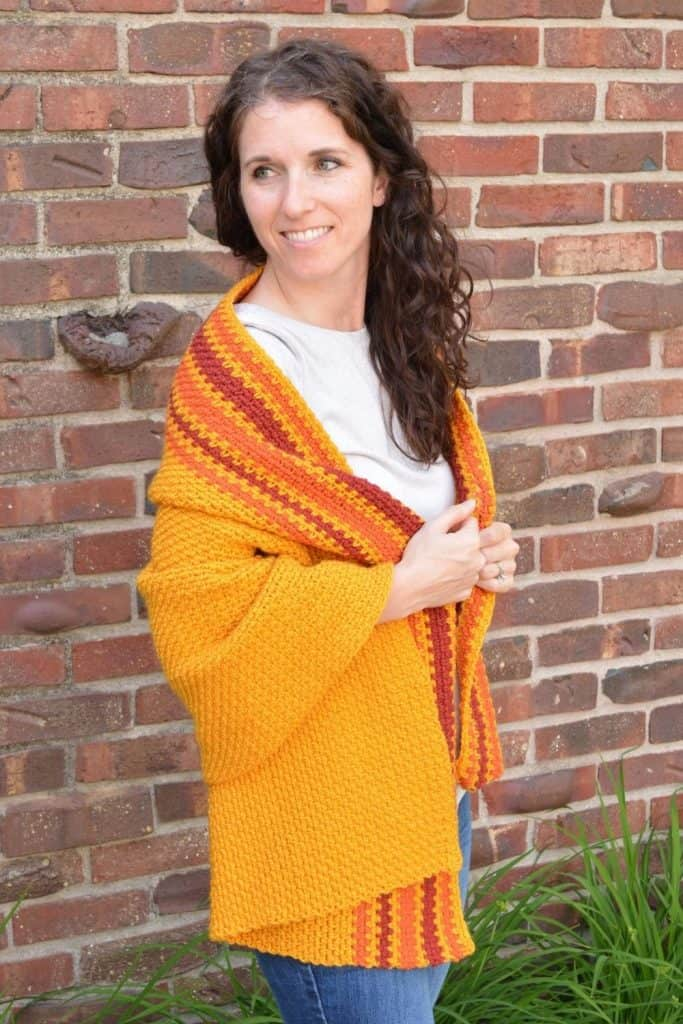 Smiling woman wrapped in a marigold crochet prayer shawl with pumpkin and burgundy stripes