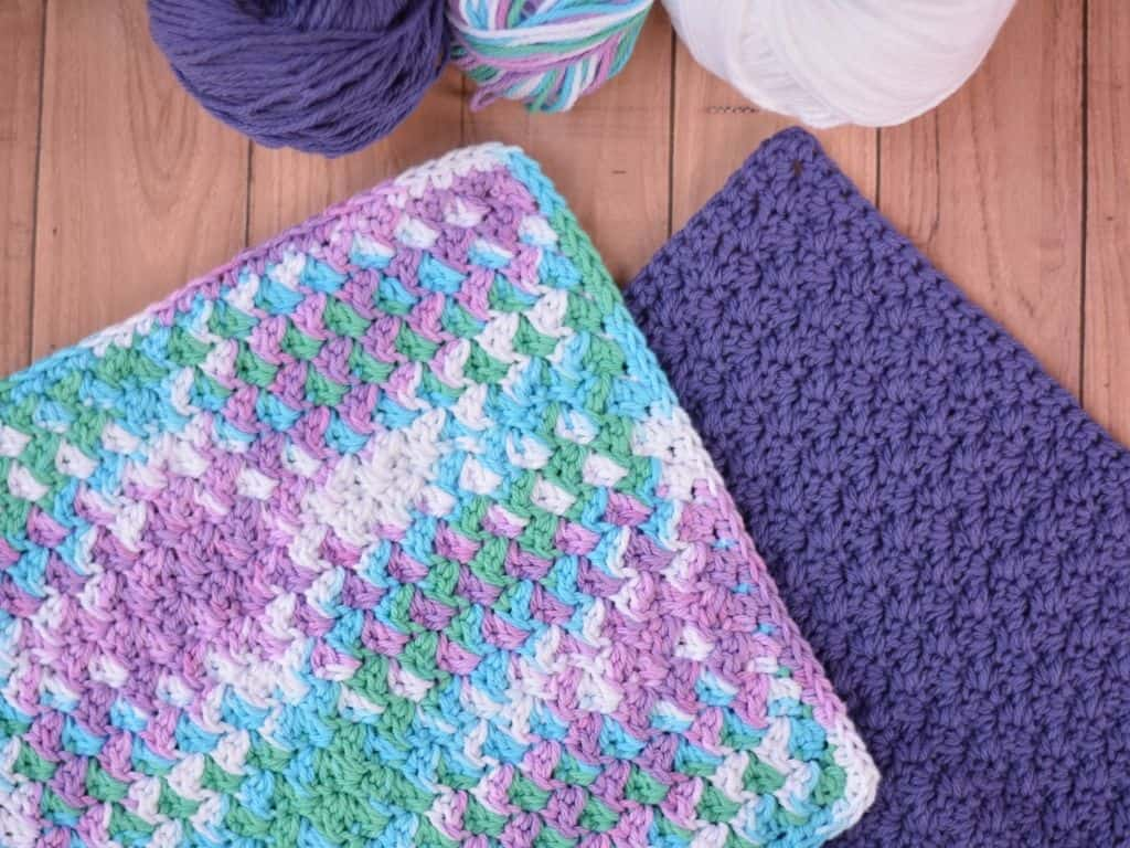 Two washcloths laid flat on a table next to skeins of yarn.