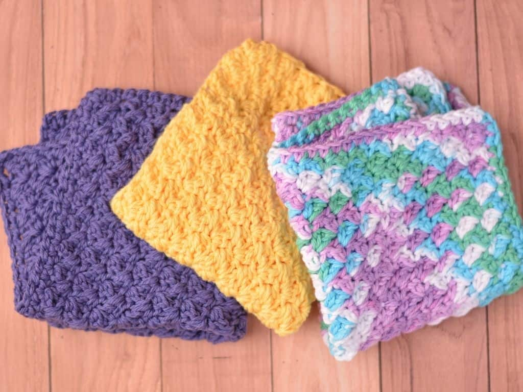 Three washcloths folded in dark orchid, yellow and beach ball blue colors
