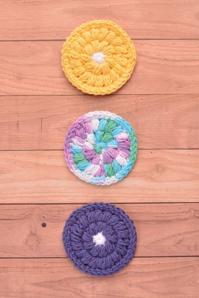 Three face scrubbies on a wooden table. Colors of yellow and dark orchid and ombre yarn.
