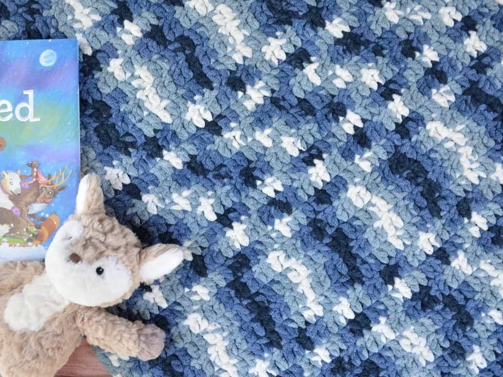 Blue crochet baby blanket with stuffed fox toy