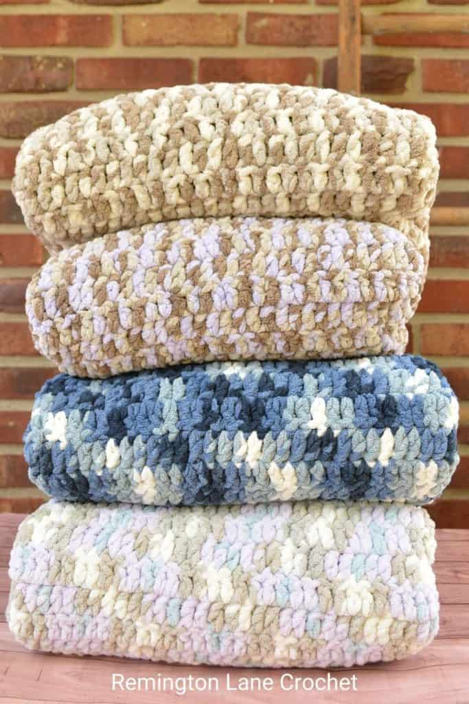 Stack of four folded crochet baby blankets.