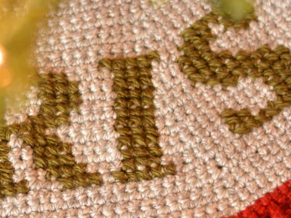 Close up of cross stitch on top of crochet tree skirt to create monogram lettering