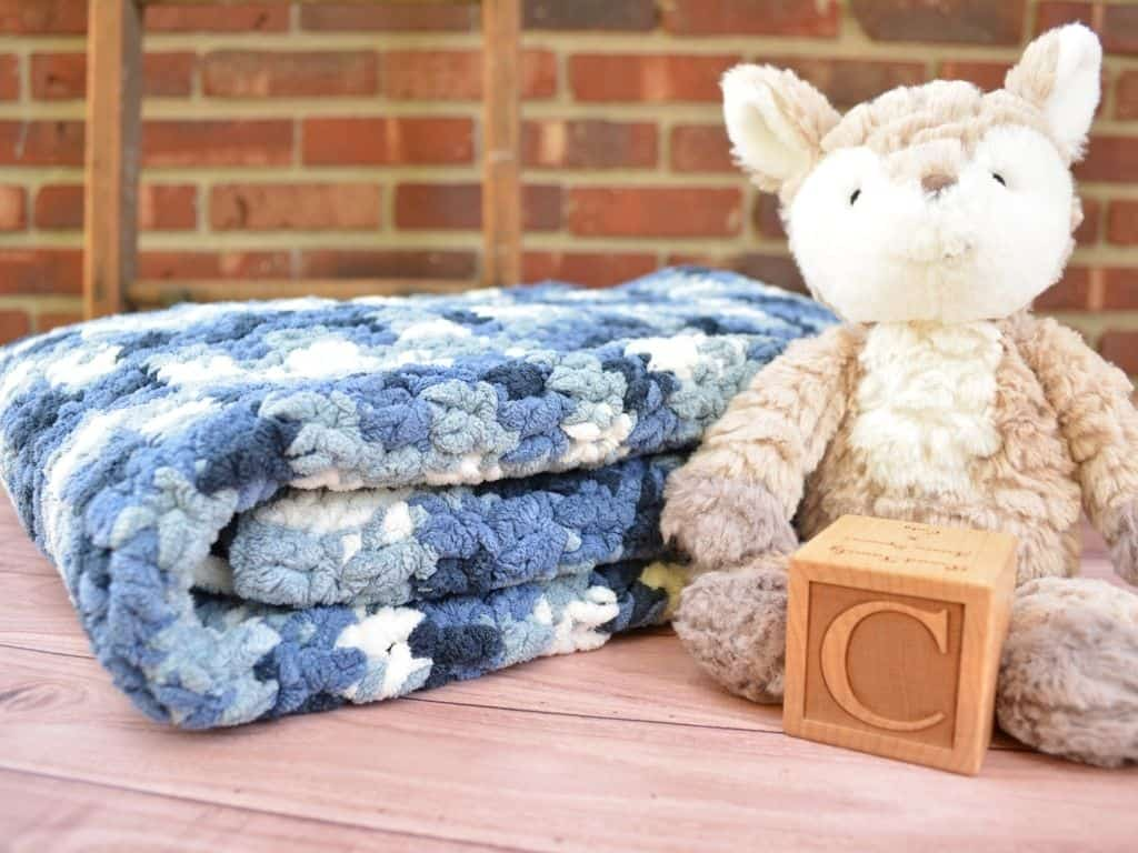 Folded baby blanket next to stuffed fox animal and wooden baby block with the letter C on it