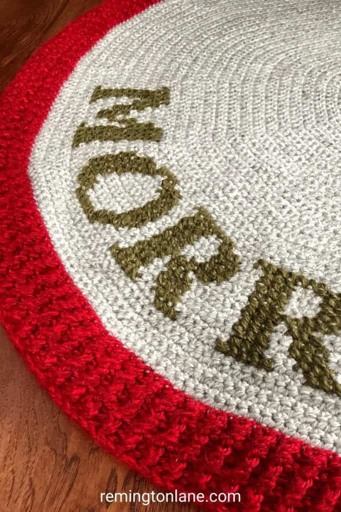 Close up of cross stitch lettering on top of a crochet tree skirt