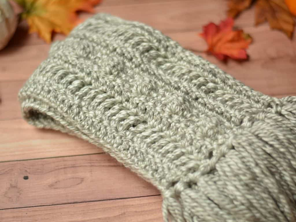 A folded rustic scarf with fall leaves in the background