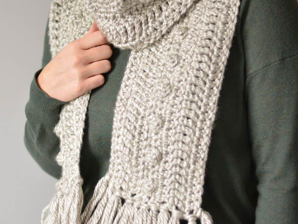 A grey crochet scarf pattern with fringe