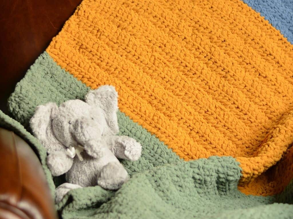 Baby blanket with large, colorful stripes, draped over the back of a chair with a stuffed elephant.