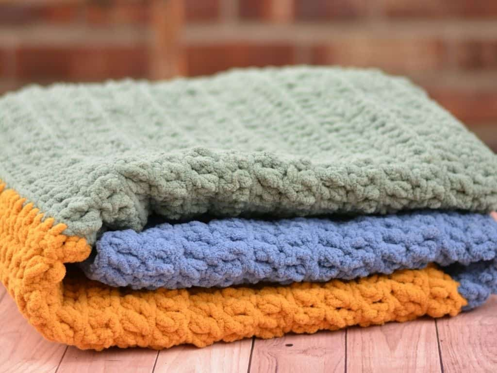 Folded blue, gold and sage baby blanket.