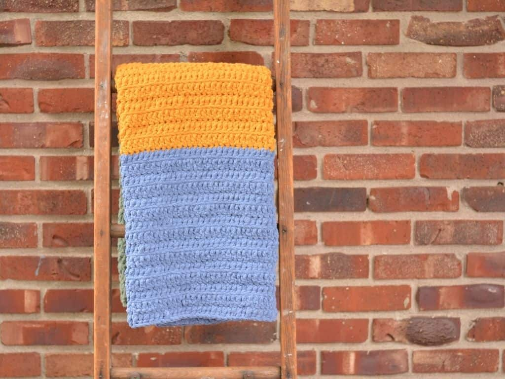 Blue and gold baby blanket draped over an antique ladder