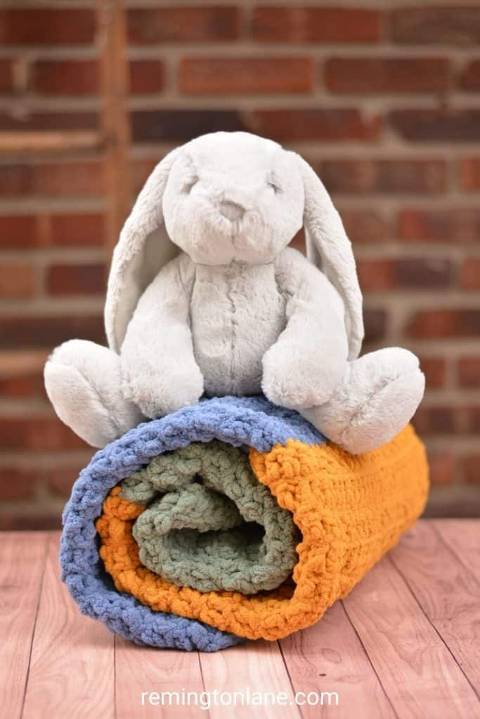 Rolled up baby blanket with a soft grey stuffed bunny sitting on top