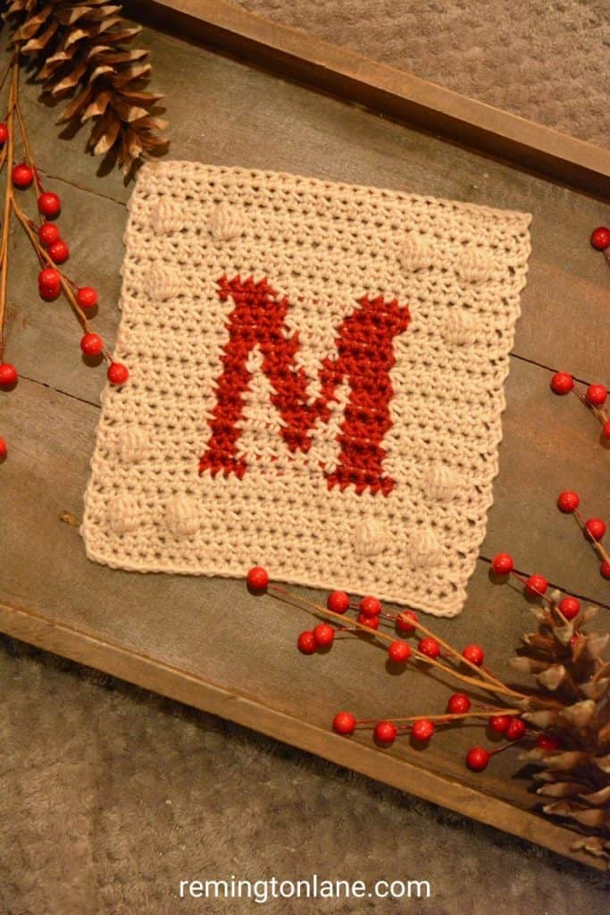Crochet blanket square in cream yarn with red monogram letter on a wooden tray.