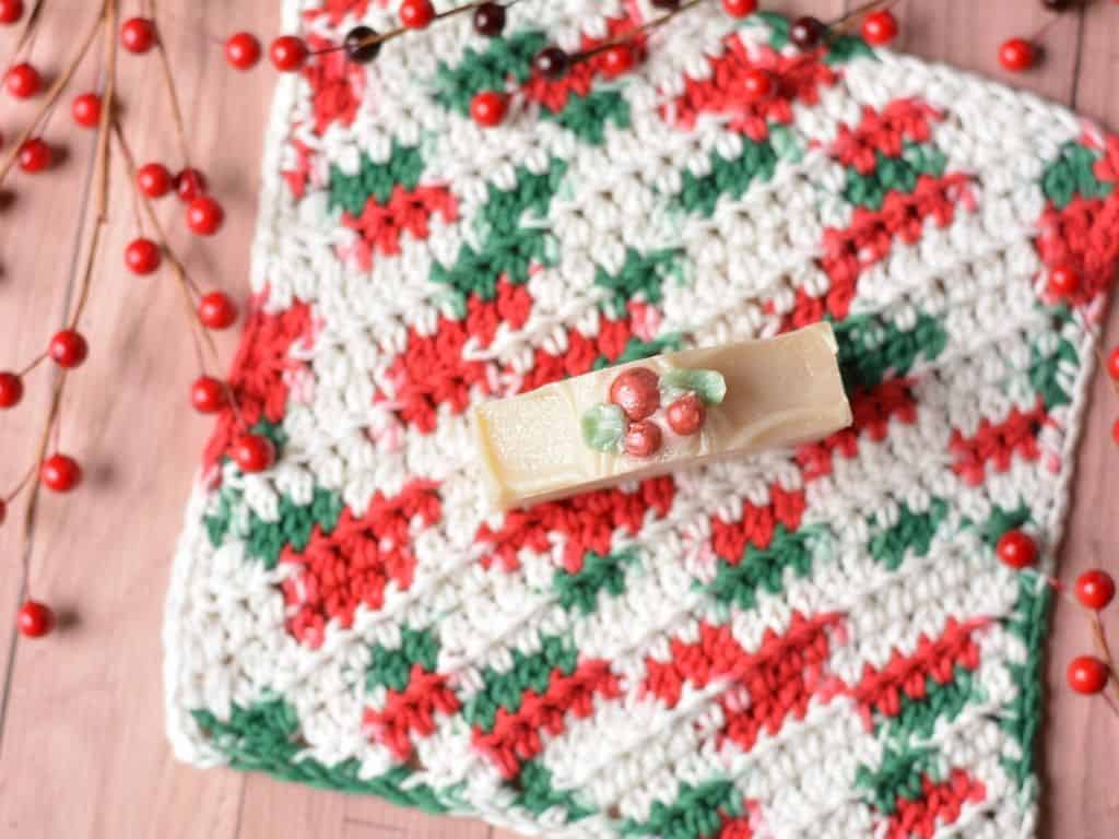 Holly berry handmade soap on top of a red, white and green variegated crochet washcloth