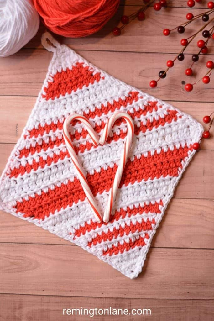 Candy canes in the shape of a heart resting on a handmade red and white striped crochet dishcloth