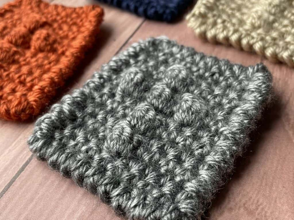 A close-up view of the cross texture made with grey yarn