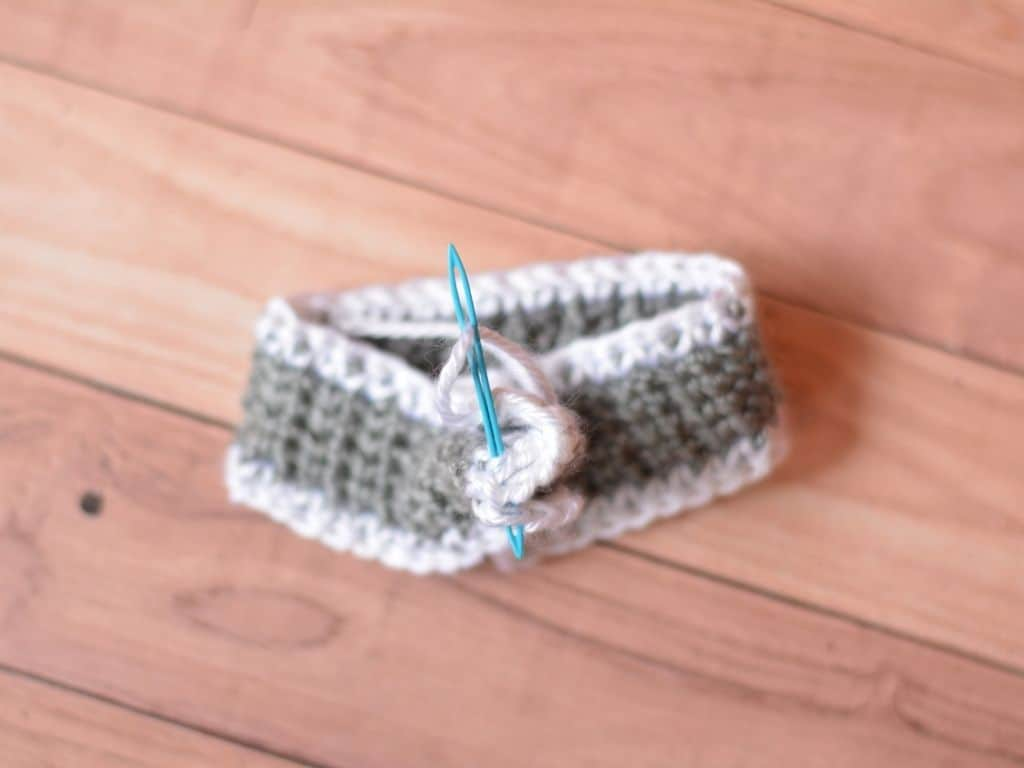 A crochet headband being sewn together into one piece